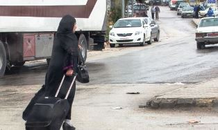 Refugee woman pulling suitcase in Beruit