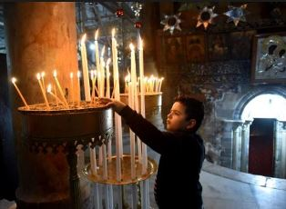 Boy lights a candle in Bethlehem