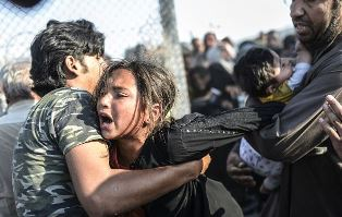 Syrian girl pulled through barbed wire fence