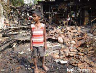 smaller young boy stands amidst the fire damage