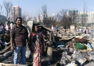 Family stand in front of damage from Mumbai fire GFA