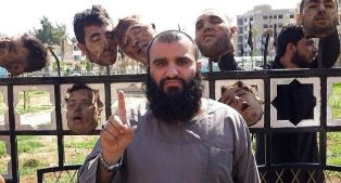 Shocking picture of ISIS fighter with heads behind him
