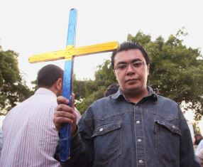 Bishoy holding a cross