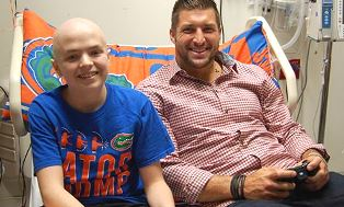 Tim Tebow with one of the children he serves