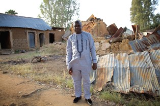 Pastor in front of home destroyed by Fulani in village where we were nearly ambushed