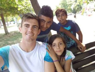 Billy Miller with kids in Romania