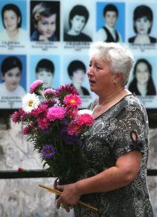 Woman brings flowers to Beslan school memorial