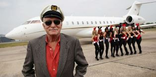 Hugh Hefner with his private plane and his bunnies