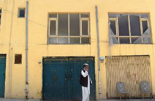 Man on phone outside guest house in Kabul smaller