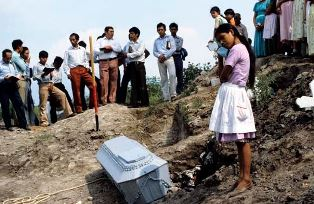 daughter watches coffin of a parent in El Salvador