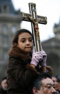 Coptic girl holds a cross smaller