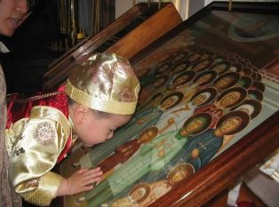 Young chinese boy kisses icon of Saints smaller