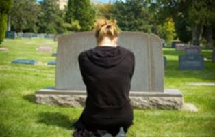 Grieving mother at graveside of her daughter