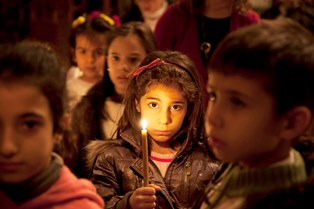 0124Syria 2 Young girl with a candle at Al Zaytoun Melkite Greek Catholic Church Damascus Syria. smaller