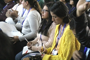 attendees take notes at Quito missions conference smaller