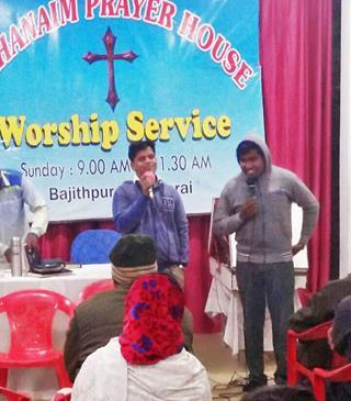 mi Pastor Ajay Kumar in blue and a student from Bethany Bible College in Kerala state at a prayer service. Morning Star News